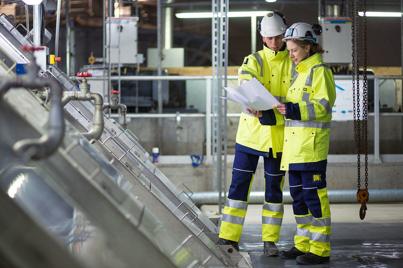Photo: one female and one male employee, wearing work clothes and concentrating on printed documents; at left, the raking system of the existing sewage treatment plant.