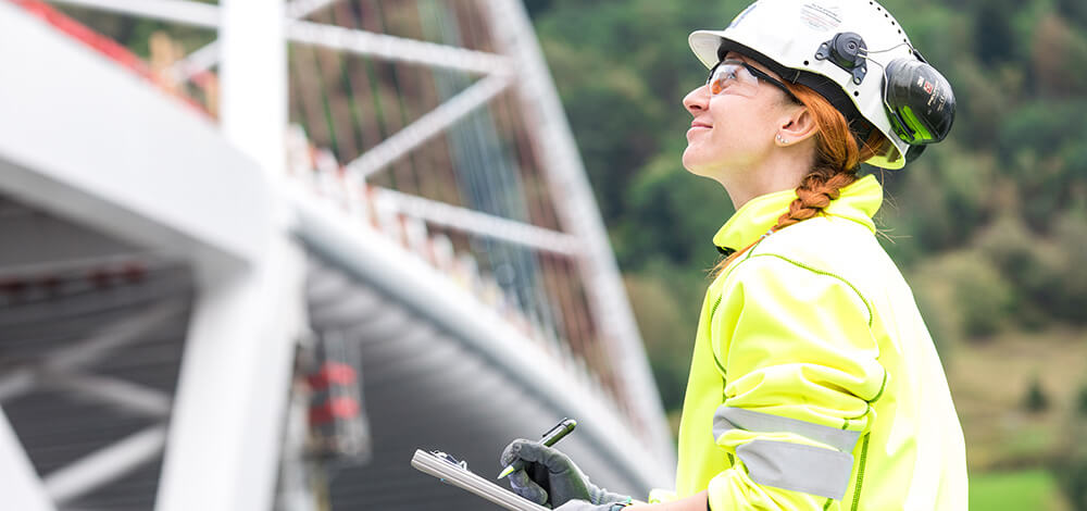 Employee working on the construction of the Loftesnes bridge is holding a clipboard and looking towards the bridge, which can be seen slightly blurred in the background.
